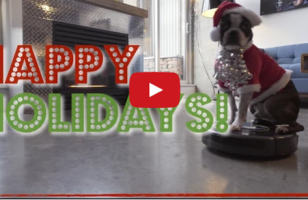 A Boston Terrier Dressed As Santa Claus Riding A Roomba